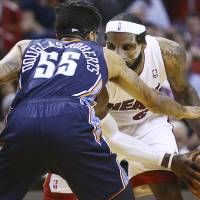 Photo - Charlotte Bobcats' Chris Douglas-Robert (55) tries to block Miami Heat's LeBron James (6) during the second half of an NBA basketball game in Miami, Monday, March 3, 2014. LeBron James scored a team recond of 61 points. The Heat won 124-107. (AP Photo/J Pat Carter)