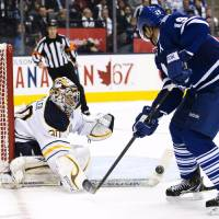 Photo - Toronto Maple Leafs forward Joffrey Lupul, right, gets spoke checked by Buffalo Sabres goalie Ryan Miller, left, during the second period of their NHL hockey game, Monday, Jan. 21, 2013, in Toronto. (AP Photo/The Canadian Press, Nathan Denette)
