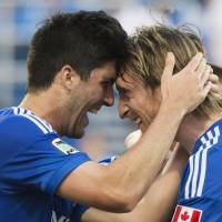 Photo - Montreal Impact's Eric Miller, left, and Gorka Larrea celebrate a goal by teammate Jack McInerney against the Houston Dynamo during the first half of an MLS soccer game in Montreal, Sunday, June 29, 2014. (AP Photo/The Canadian Press, Graham Hughes)