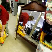 Photo - Employee Nathan Putnam mops the floor at ReRun Junction, a Norman thrift store run by disabled adults. PHOTO BY STEVE SISNEY, THE OKLAHOMAN  STEVE SISNEY