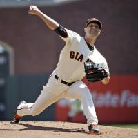 Photo - San Francisco Giants starter Tim Hudson throws to the Colorado Rockies during the first inning of a baseball game on Sunday, April 13, 2014, in San Francisco. (AP Photo/Marcio Jose Sanchez)