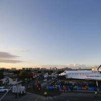 Photo -   The space shuttle Endeavour sits in a strip mall near Los Angeles International Airport in Los Angeles, Friday, Oct. 12, 2012. Endeavour's 12-mile road trip kicked off shortly before midnight Thursday as it moved from its Los Angeles International Airport hangar en route to the California Science Center, its ultimate destination, said Benjamin Scheier of the center. (AP Photo/Jae C. Hong)