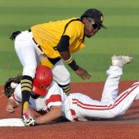 Photo - Kennesaw State's Cornell Nixon, top, tags Louisville's Nick Solak out as he attempted to steal second base in the third inning of an NCAA college baseball tournament super regional game in Louisville, Ky., Friday, June 6, 2014. (AP Photo/Timothy D. Easley)
