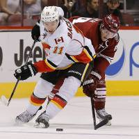 Photo - Calgary Flames' Mikael Backlund (11) battles Phoenix Coyotes' Shane Doan for the puck during the first period of an NHL hockey game on Saturday, March 15, 2014, in Glendale, Ariz. (AP Photo/Matt York)
