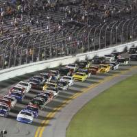 Photo - Trevor Bayne, front left, and Dakoda Armstrong, front right, lead the field to start the  NASCAR Nationwide series auto race at Daytona International Speedway in Daytona Beach, Fla., Friday, July 4, 2014. (AP Photo/David Graham)