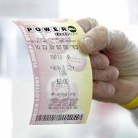 Photo - FILE - This Nov. 28, 2012, file photo shows a customer at a 7-Eleven convenience store with a Powerball ticket in Tampa, Fla. The jackpot for the latest drawing on Wednesday, May, 15, 2013, has ballooned to an estimated $360 million, with a cash value of $229.2 million, making it the third largest Powerball jackpot and the seventh largest jackpot ever. (AP Photo/Chris O'Meara, File)