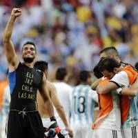 Photo - CORRECTS PHOTOGRAPHER'S BYLINE - Argentina goalkeeper Sergio Romero, left, and teammates celebrate at the end of the World Cup quarterfinal soccer match between Argentina and Belgium at the Estadio Nacional in Brasilia, Brazil, Saturday, July 5, 2014. Argentina won 1-0. (AP Photo/Eraldo Peres)