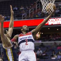 Photo - Washington Wizards point guard John Wall (2) drives to the basket against Utah Jazz center Enes Kanter during the first half of an NBA basketball game on Wednesday, March 5, 2014, in Washington. (AP Photo/ Evan Vucci)