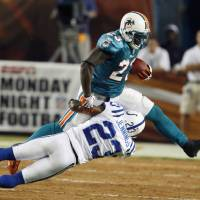 Photo - Miami Dolphins running back Ronnie Brown is taken down by Indianapolis Colts safety Tim Jennings during the first quarter of an NFL football game Monday, Sept. 21, 2009, in Miami. (AP Photo/Wilfredo Lee) ORG XMIT: LSS107