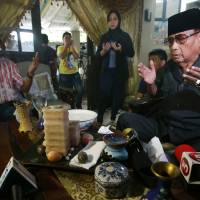 Photo - Filipino Sultan Jamalul Kiram III, right, prays at his residence in suburban Taguig, south of Manila, Philippines on Sunday, March 3, 2013. Malaysia's police chief said at least seven people have been killed in a shootout between police and suspected Filipino members of the Muslim royal clan on Borneo island. (AP Photo/Aaron Favila)