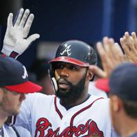 Photo - Atlanta Braves' Jason Heyward celebrates with his teammates in the dugout after hitting a home run in the second inning of a baseball game against the Philadelphia Phillies in Atlanta, Friday, July 18, 2014. (AP Photo/John Bazemore)