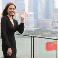 Photo - Actress Angelina Jolie waves during a promotion tour for her movie