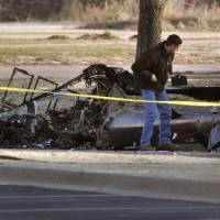 Photo - Investigators with the FAA look over the wreckage of a medical helicopter which crashed Friday, Feb. 22, 2013 in front of the Saint Ann Retirement Center in Oklahoma City, Okla. Two people were killed in the crash and a third person was injured.  (AP Photo/The Oklahoman,Paul Hellstern) LOCAL TV OUT (KFOR, KOCO, KWTV, KOKH, KAUT OUT); LOCAL INTERNET OUT; LOCAL PRINT OUT (EDMOND SUN OUT, OKLAHOMA GAZETTE OUT) TABLOIDS OUT