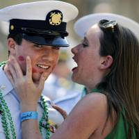 Photo - U.S Coast Guard Petty Officer 3rd Class Tanner Marshall is kissed by a woman during a St. Patrick's Day parade, Saturday, March, 16, 2013, in Savannah, Ga. St. (AP Photo/Stephen Morton)
