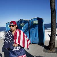 Photo - A fan of the U.S. national soccer team walks by the seaside with a U.S. flag draped over his shoulders, in Salvador, Brazil, Monday, June 30, 2014. Salvador is one of the host cities of the FIFA 2014 Soccer World Cup. (AP Photo/Rodrigo Abd)