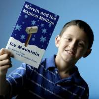 Photo -  Brendan  Frias holds a book he wrote with his father Aaron  Frias, at the OPUBCO Studios, July 28, 2009. Photo by Sarah Phipps