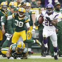 Photo - Minnesota Vikings running back Adrian Peterson breaks away from Green Bay Packers' Tramon Williams (38) and Mike Neal (96) for an 82-yard touchdown run during the first half of an NFL football game Sunday, Dec. 2, 2012, in Green Bay, Wis. (AP Photo/Tom Lynn)