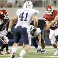 Photo - OU's Landry Jones looks for room during the college football game between the Brigham Young University Cougars (BYU) and the University of Oklahoma Sooners (OU) at Cowboys Stadium in Arlington, Texas, Saturday, September 5, 2009. By Bryan Terry, The Oklahoman ORG XMIT: KOD