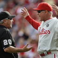 Photo - Philadelphia Phillies manager Ryne Sandberg (23) argues a reviewed call at home with umpire Tom Hallion (20) in the sixth inning of a baseball game against the Cincinnati Reds, Saturday, June 7, 2014, in Cincinnati. Sandberg was ejected from the game. (AP Photo/Al Behrman)