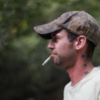 Photo - Johnny Heskett, of McAlester, smokes a cigarette during a hunting trip near Indianola, Okla., Friday, July 6, 2012.  Photo by Garett Fisbeck, The Oklahoman