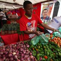 Photo - A vendor wearing a T-shirt with an image of Venezuela's President Hugo Chavez sells vegetable at a state-run market in Caracas, Venezuela, Friday, Dec. 28, 2012. The obsessive, circular conversations about Chavez's health dominate family dinners, plaza chit-chats and social media sites in this country on edge since its larger-than-life leader went to Cuba for emergency cancer surgery more than two weeks ago. The man whose booming voice once dominated the airwaves for hours at a time has not been seen or heard from since.(AP Photo/Fernando Llano)