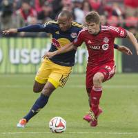 Photo - Toronto FC's Nick Hagglund, right, tussles with New York Red Bulls' Thierry Henry  during the first half of an MLS soccer game in Toronto on Saturday, May 17, 2014. (AP Photo/The Canadian Press, Chris Young)