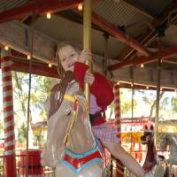 Photo - Miranda Price rides the 1918 carousel at Kiddie Park in San Antonio. Photo by Annette Price, for The Oklahoman.