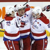 Photo - Washington Capitals' Alex Ovechkin (8), John Carlson (74) and Troy Brouwer (20) celebrate Ovechkin's goal against the Winnipeg Jets during the third period of an NHL hockey game in Winnipeg, Manitoba, on Thursday, March 21, 2013. The Capitals won 4-0. (AP Photo/The Canadian Press, John Woods)
