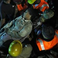 Photo - Rescuers carry an injured woman worker  pulled out from the rubble of a building that collapsed on the outskirts of Chennai, India, Sunday, June 29, 2014. The 12-story apartment structure the workers were building collapsed late Saturday while heavy rains and lightning were pounding. Police said 31 construction workers had been pulled out so far and the search was continuing for more than a dozen others. (AP Photo/Arun Sankar K)