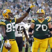 Photo -   Green Bay Packers wide receiver Greg Jennings celebrates a touchdown reception with guard T.J. Lang during the first half of an NFL football game against the New Orleans Saints on Sunday, Sept. 30, 2012, in Green Bay, Wis. (AP Photo/Mike Roemer)