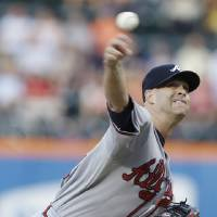 Photo - Atlanta Braves' Tim Hudson delivers a pitch during the first inning of a baseball game against the New York Mets, Wednesday, July 24, 2013, in New York. (AP Photo/Frank Franklin II)