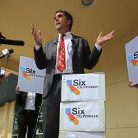 Photo - Silicon Valley venture capitalist Tim Draper talks to reporters next to six boxes of petitions for a ballot initiative that would ask voters to split California into six separate states, before turning them into the Sacramento County Registrar of Voters,  Tuesday, July 15, 2014, in Sacramento, Calif.  Draper delivered what he said were 44,000 signatures, of the 1.3 million the Six California's campaign plans to submit statewide this week.  If enough signatures are verified,  voters in November 2016 would be asked to divide the state into six states called Jefferson, North California, Silicon Valley, Central California, West California and South California. (AP Photo/Rich Pedroncelli)