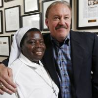 Photo -  Sister Rosemary Nyirumbe and Oklahoma City attorney Reggie Whitten, founder of Pros for Africa, pose for a photo at the Whitten Newman Foundation offices in Oklahoma City. Photo by Nate Billings, The Oklahoman   NATE BILLINGS -