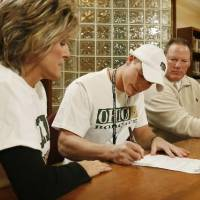 Photo - Tyler Tettleton signs a letter of intent to play college football while his mother Sylvia Nettleton and father Mickey Tettleton watch at Norman North High School in Norman, Okla. on Wednesday, Feb. 4, 2009. Photo by Steve Sisney