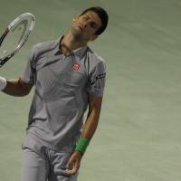 Photo - Novak Djokovic of Serbia reacts after he missed a ball against Roger Federer of Switzerland during a semi final match of the Dubai Tennis Championships in Dubai, United Arab Emirates, Friday, Feb. 28, 2014. (AP Photo/Kamran Jebreili)