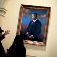 Photo - Rep. Roger Bruce, D-Atlanta, left, points out the hanging portrait of Rev. Martin Luther King Jr., to his assistant, Sophia Andrade, following a service celebrating King's birthday inside the Georgia State Capitol, Thursday, Jan. 17, 2013, in Atlanta. (AP Photo/David Goldman)