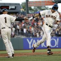 Photo - San Francisco Giants' Tyler Colvin, right, shakes hands with third base coach Tim Flannery, left, after Colvin's solo home run against the Atlanta Braves during the second inning of a baseball game on Monday, May 12, 2014, in San Francisco. (AP Photo/Marcio Jose Sanchez)