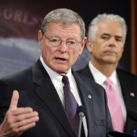 Photo - JIM INHOFE: Sen. John Ensign, R-Nev. looks on at right, as Sen. James Inhofe, R-Okla., speaks during a news conference to discuss TARP, Wednesday, April 22, 2009, on Capitol Hill in Washington. (AP Photo/Susan Walsh) ORG XMIT: DCSW115