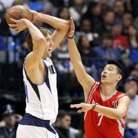 Photo - Dallas Mavericks forward Dirk Nowitzki (41) looks to pass as Houston Rockets guard Jeremy Lin (7) defends during the first half of an NBA basketball game, Wednesday, Jan. 16, 2013, in Dallas. (AP Photo/John F. Rhodes)