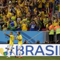 Photo - Brazil's Neymar, second left, celebrates scoring the opening goal during the group A World Cup soccer match between Cameroon and Brazil at the Estadio Nacional in Brasilia, Brazil, Monday, June 23, 2014. (AP Photo/Dolores Ochoa)