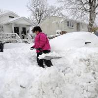 Photo - April Palmieri digs out her car in front of her home, background left, on 17th Street after a snow storm on Saturday, Feb. 9, 2013 in Bayville, N.Y. Palmieri had five feet of water in her basement as result of the rains from Superstorm Sandy. A howling storm across the Northeast left the New York-to-Boston corridor shrouded in 1 to 3 feet of snow Saturday, stranding motorists on highways overnight and piling up drifts so high that some homeowners couldn't get their doors open. More than 650,000 homes and businesses were left without electricity. (AP Photo/Kathy Kmonicek)