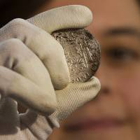 Photo - A worker of the ministry holds up for photographers a silver coin from the shipwreck of a 1804 galleon, on its first display to the media at a ministry building, in Madrid, Friday, Nov. 30, 2012. Spanish cultural officials have allowed the first peep at 16 tons (14.5 metric tons) of the shipwreck, 'Nuestra Senora de las Mercedes' a treasure worth an estimated $500 million that a U.S. salvage company gave up after a five-year international ownership dispute. (AP Photo/Daniel Ochoa de Olza)