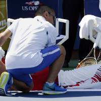Photo - Ivan Dodig, of Croatia, is treated by a trainer during an injury timeout during the second round of the 2014 U.S. Open tennis tournament against Feliciano Lopez, of Spain, Wednesday, Aug. 27, 2014, in New York. Dodig forfeited the match to Lopez in the fifth set. (AP Photo/Kathy Willens)