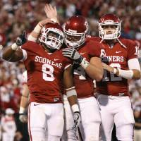 Photo - CELEBRATION: Oklahoma's Dominique Whaley (8), Gabe Ikard (64), and Landry Jones (12) celebrate after a touchdown during the college football game between the University of Oklahoma Sooners (OU) and the Ball State Cardinals at Gaylord Family-Oklahoma Memorial Stadium on Saturday, Oct. 01, 2011, in Norman, Okla. Photo by Bryan Terry, The Oklahoman  ORG XMIT: KOD
