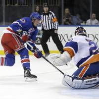 Photo - New York Rangers' J.T. Miller, left, scores a goal past New York Islanders goalie Evgeni Nabokov, right, during the second period of the NHL hockey game in New York, Thursday, Feb. 7, 2013.  (AP Photo/Seth Wenig)