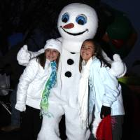 Photo - Right: A snowman hugs Kyla Vogel and Elizabeth Duncan at last year's city-sponsored Holiday Celebration at Andrews Park.