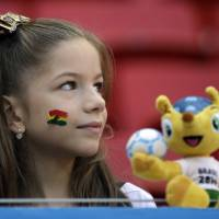 Photo - A young girl waits with the mascot 'Fuleco' for the start of the group G World Cup soccer match between Portugal and Ghana at the Estadio Nacional in Brasilia, Brazil, Thursday, June 26, 2014. (AP Photo/Martin Mejia)