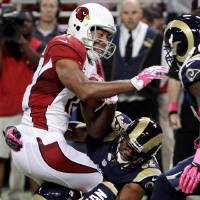 Photo -   Arizona Cardinals wide receiver Larry Fitzgerald is stopped by St. Louis Rams cornerbacks Cortland Finnegan (31) and Bradley Fletcher (32) after catching a pass during the first quarter of an NFL football game, Thursday, Oct. 4, 2012, in St. Louis. (AP Photo/Seth Perlman)
