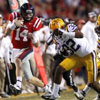 Photo -   Mississippi quarterback Bo Wallace (14) carries as LSU cornerback Jalen Collins (32) pursues in the second half of their NCAA college football game in Baton Rouge, La., Saturday, Nov. 17, 2012. LSU won 41-35. (AP Photo/Gerald Herbert)