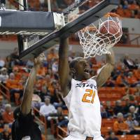 Photo -   Oklahoma State forward Kamari Murphy dunks in front of Portland State guard Marcus Hall, left, in the first half of an NCAA college basketball game in Stillwater, Okla., Sunday, Nov. 25, 2012. (AP Photo/Sue Ogrocki)